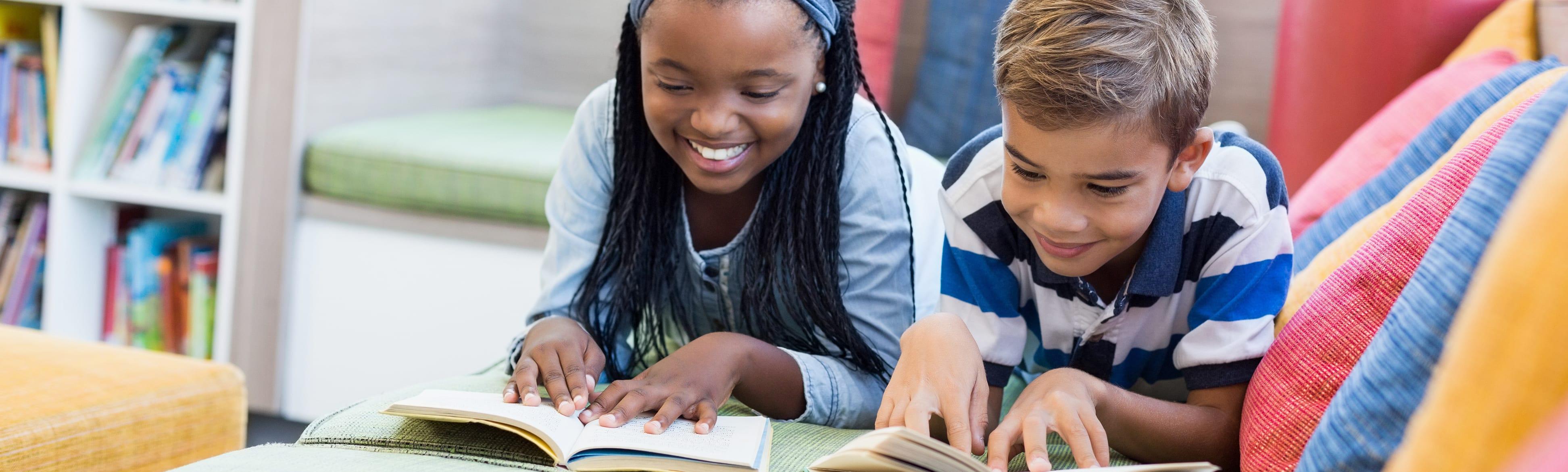 Children reading the book in summer park